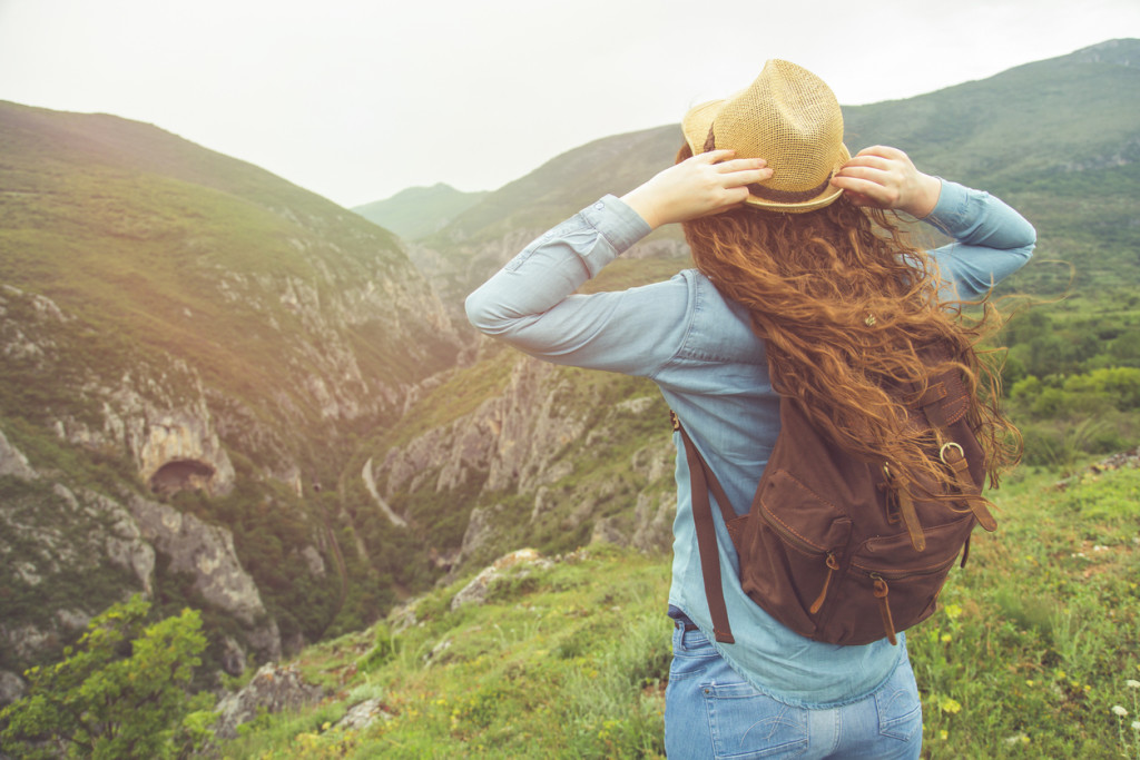 Young beautiful woman with a straw hat and a backpack standing on the top of the gorge and enjoying the view