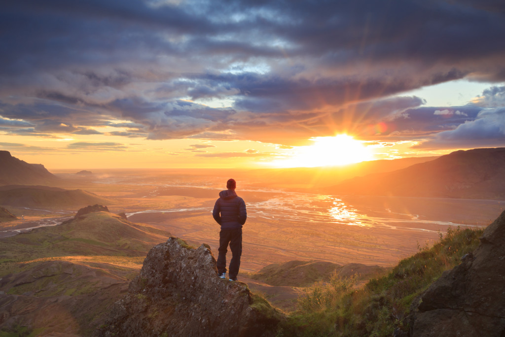 Man standing on a ledge of a mountain, enjoying the sunset over a river valley in Thorsmork, Iceland.