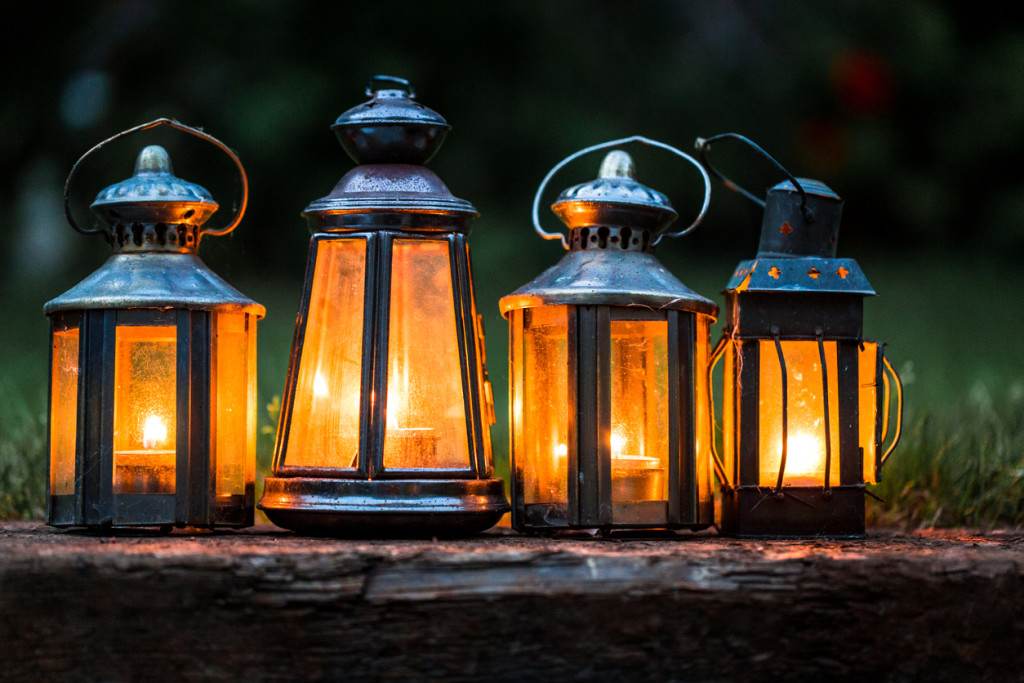 Four illuminated lanterns in a row outdoors in garden