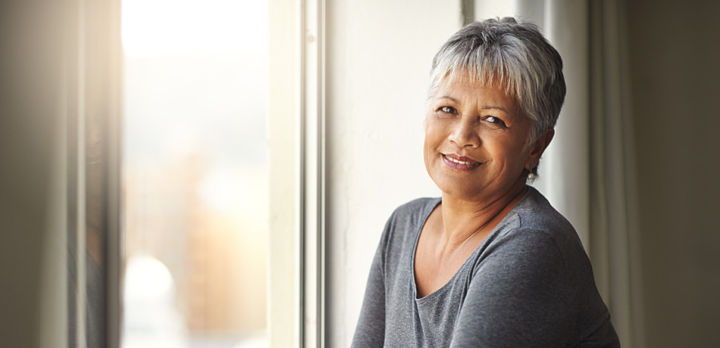 Shot of a mature woman standing by a window on a sunny day