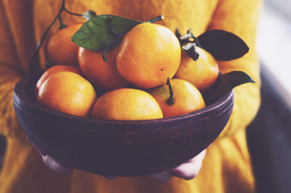 Woman with wooden bowl full of ripe winter clementines