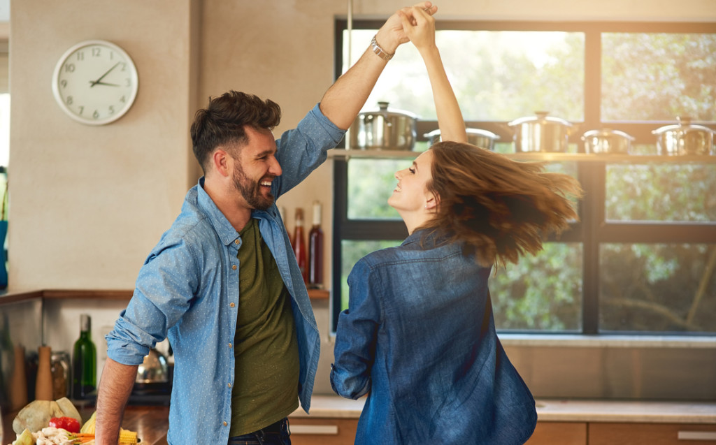 Happy young couple dancing together at home