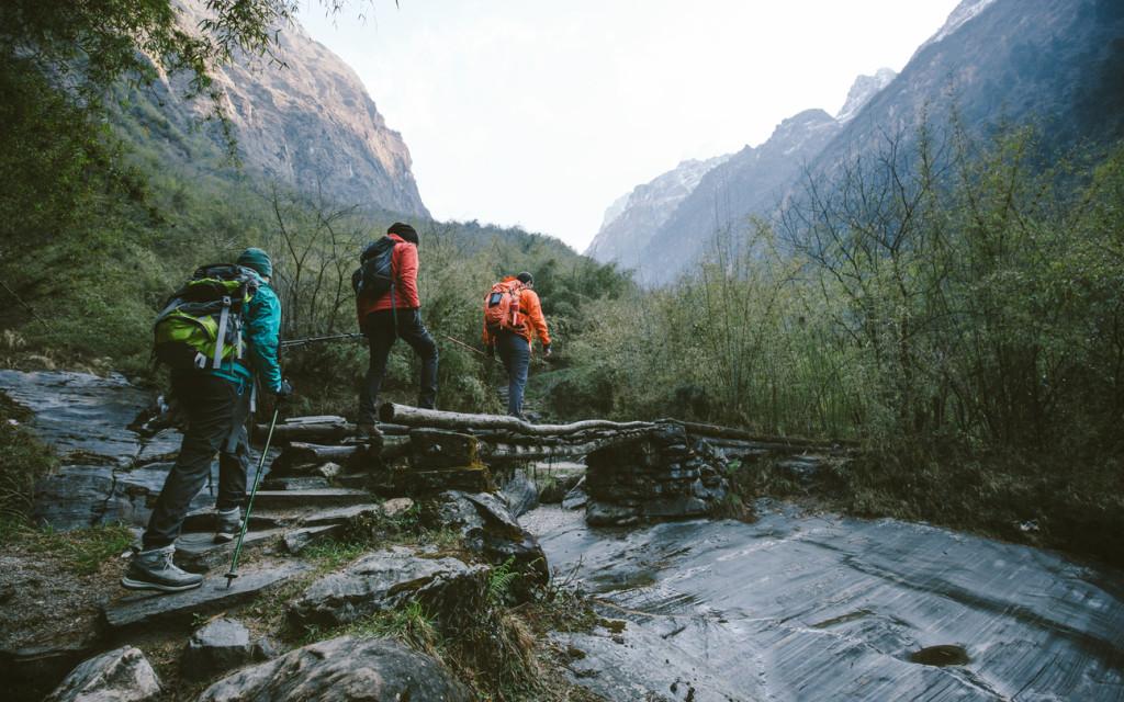 Group of trekkers cross the bridge at Annapurna region on Himalayas.