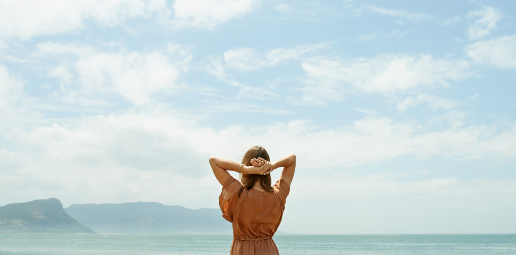 Rearview shot of a woman looking out at the ocean with sky above