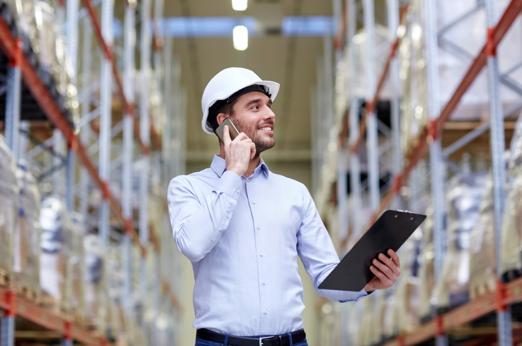 man with clipboard and smartphone at warehouse