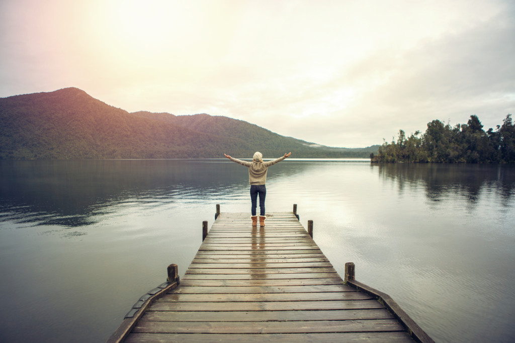 Young woman relaxes on lake pier, stands arms outstretched for freedom and positive emotions. Beautiful Autumn day in New Zealand.
