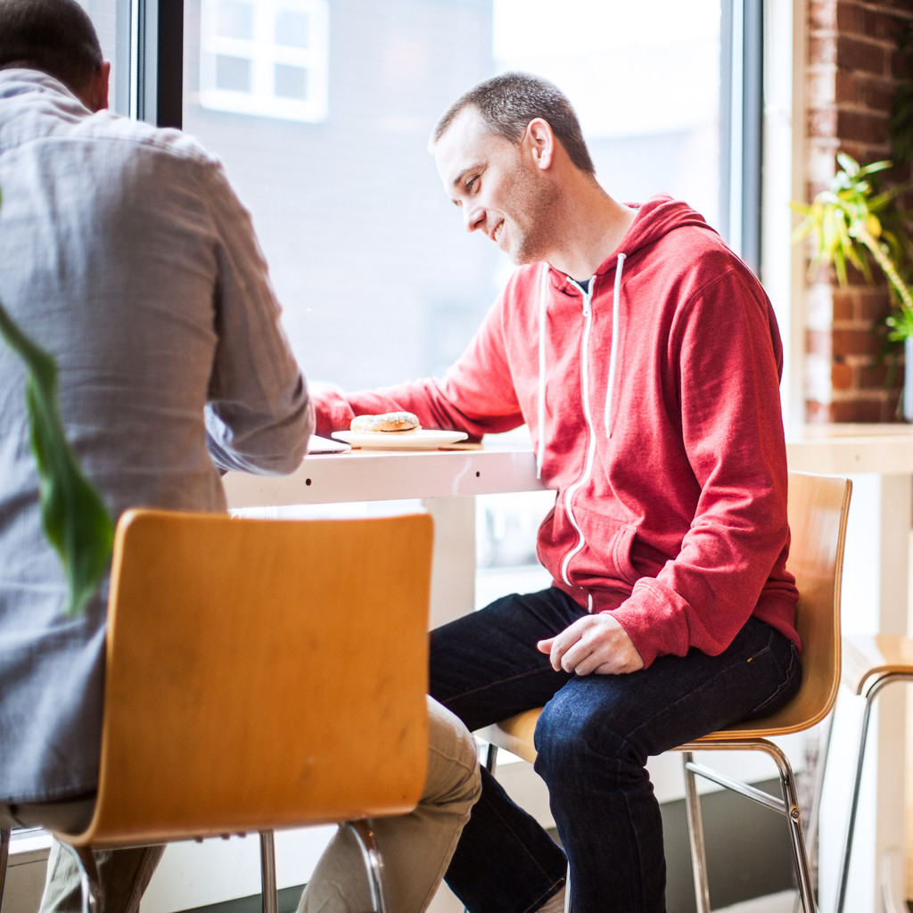 Two men meet for discussion and casual business in a clean contemporary cafe, bright white light coming in through the bay windows. They are drinking coffee as one man shows the other something on his tablet touchscreen computer. Square crop.