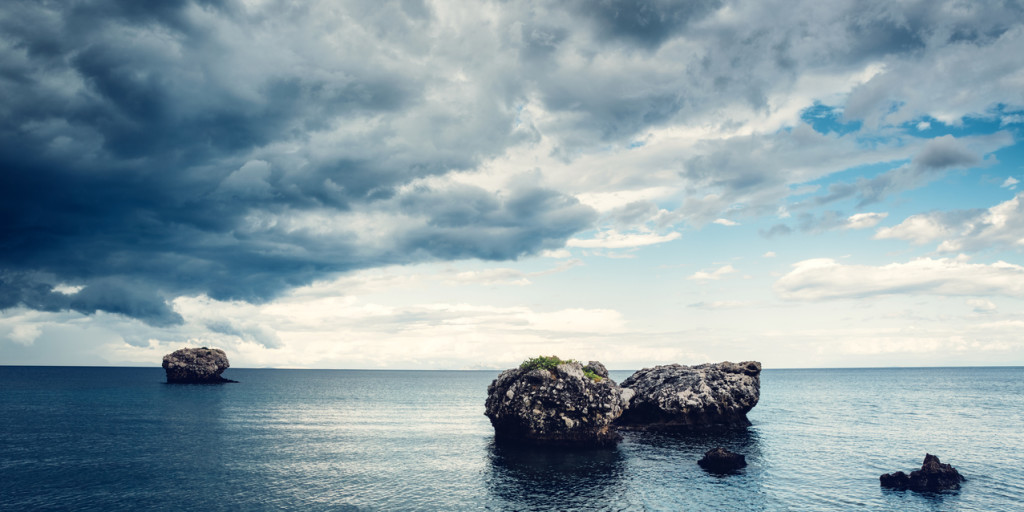 Rocks In The Sea With Dramatic Clouds