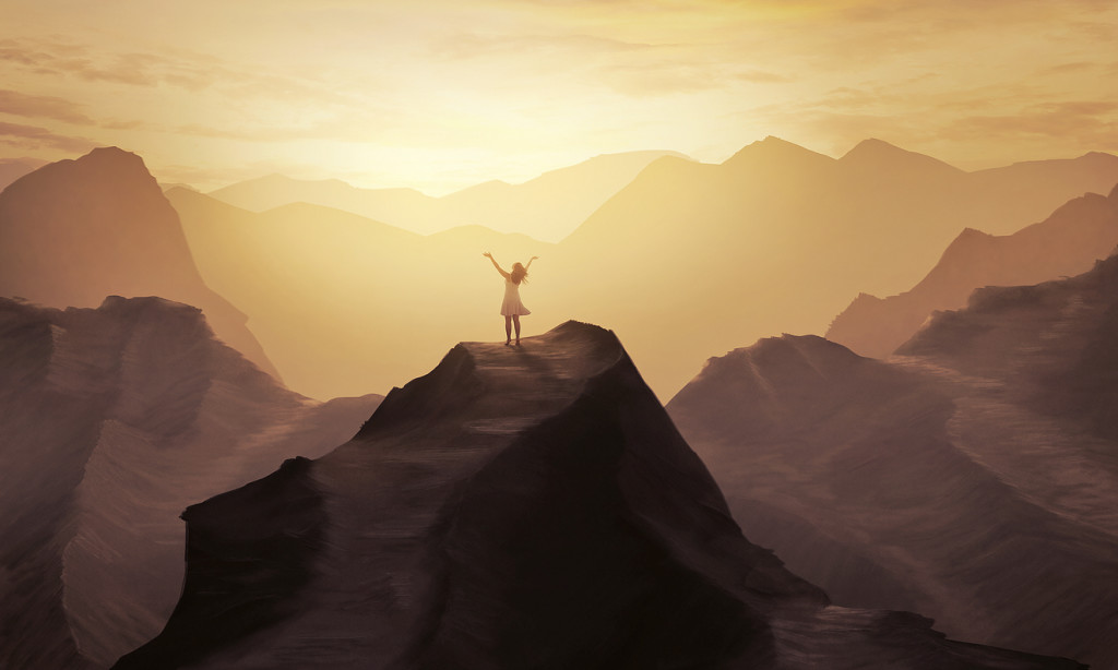 A woman stands alone on a mountain with her hands in praise.