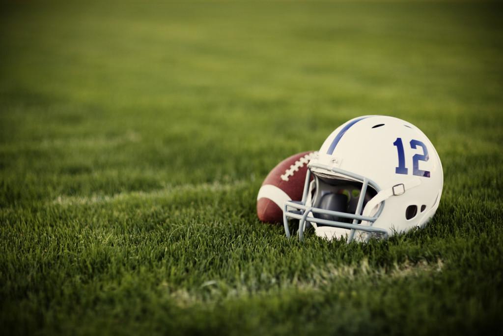 A vintage style American football helmet and football on the football field.