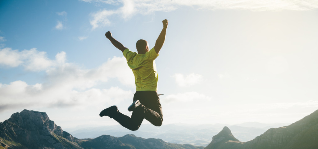 Freedom. Man jumping in the air with mountain landscape on background.