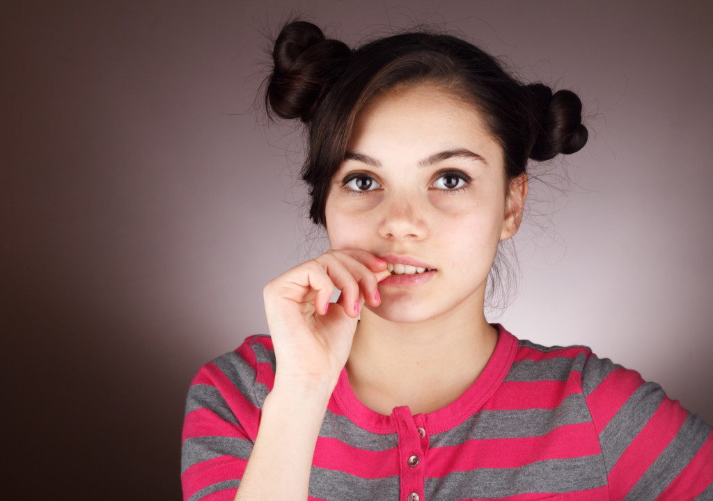 Worried young girl biting nail