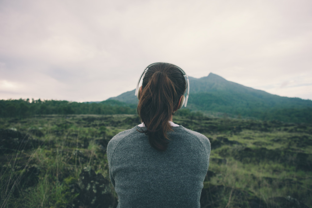 Woman in headphones listening music in nature