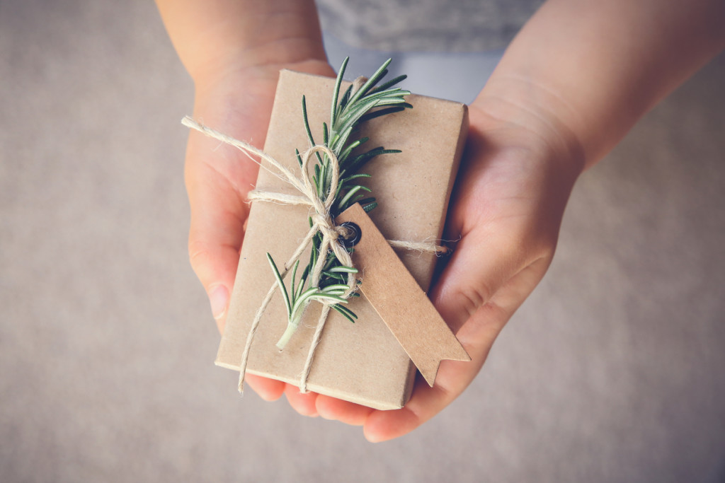 Kid holding rustic gift box with brown tag