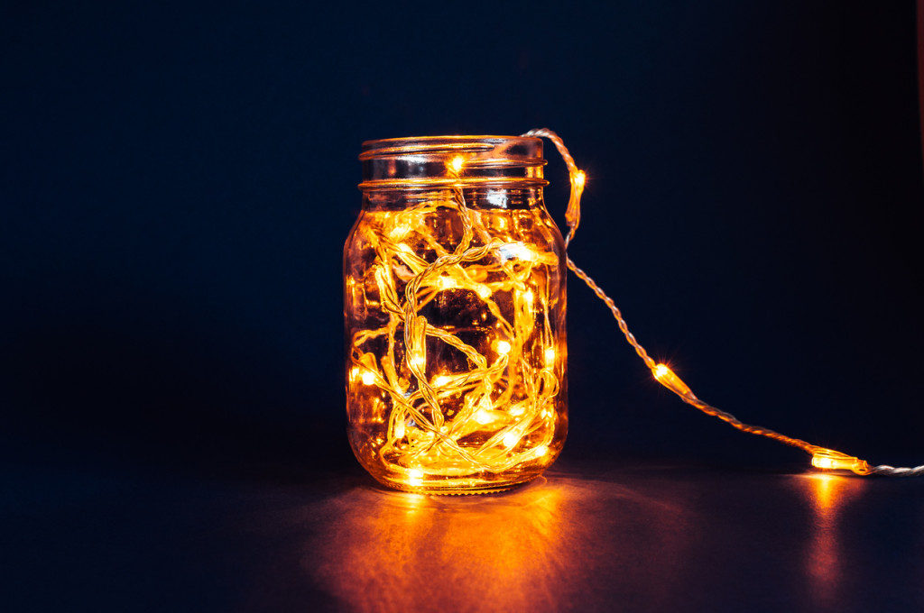Christmas fairy lights in a mason jar, glowing in the dark