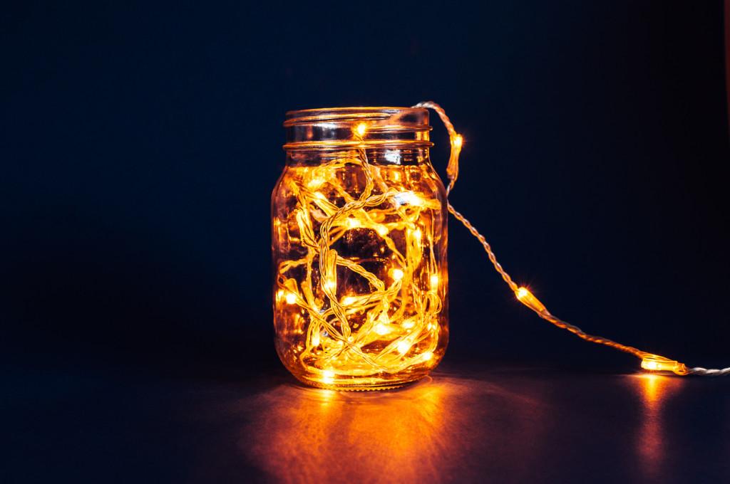 Christmas fairy lights in a mason jar, glowing in the dark