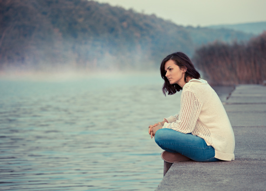 Young woman sitting by lake in the early morning.