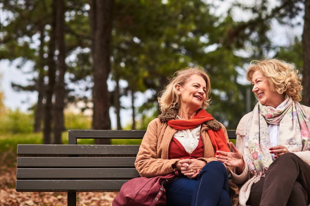 Two senoir woman laughing at the park