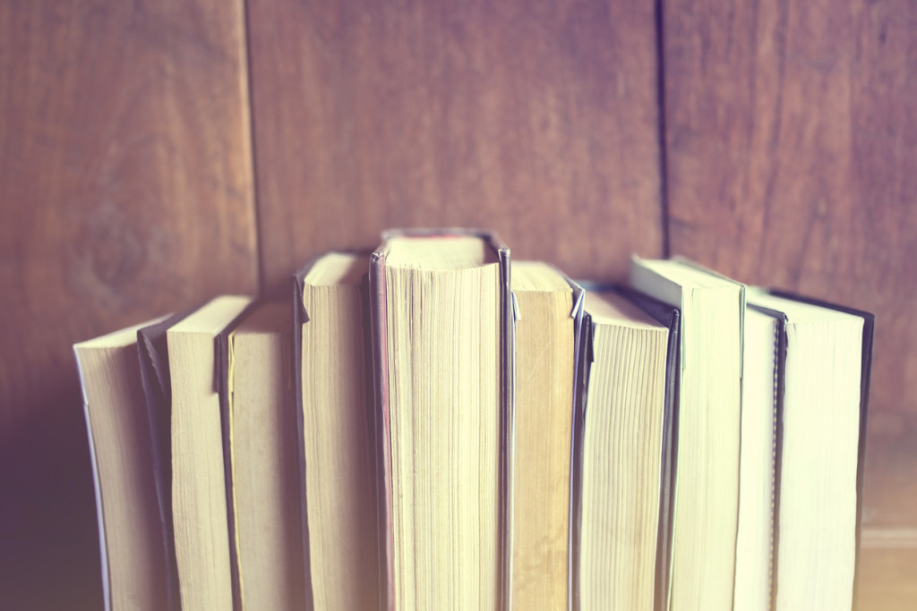Books on a wooden background, vintage color effect