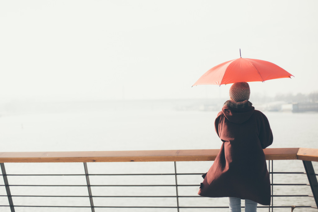Woman standing at the balcony looking at the river and holding umbrella