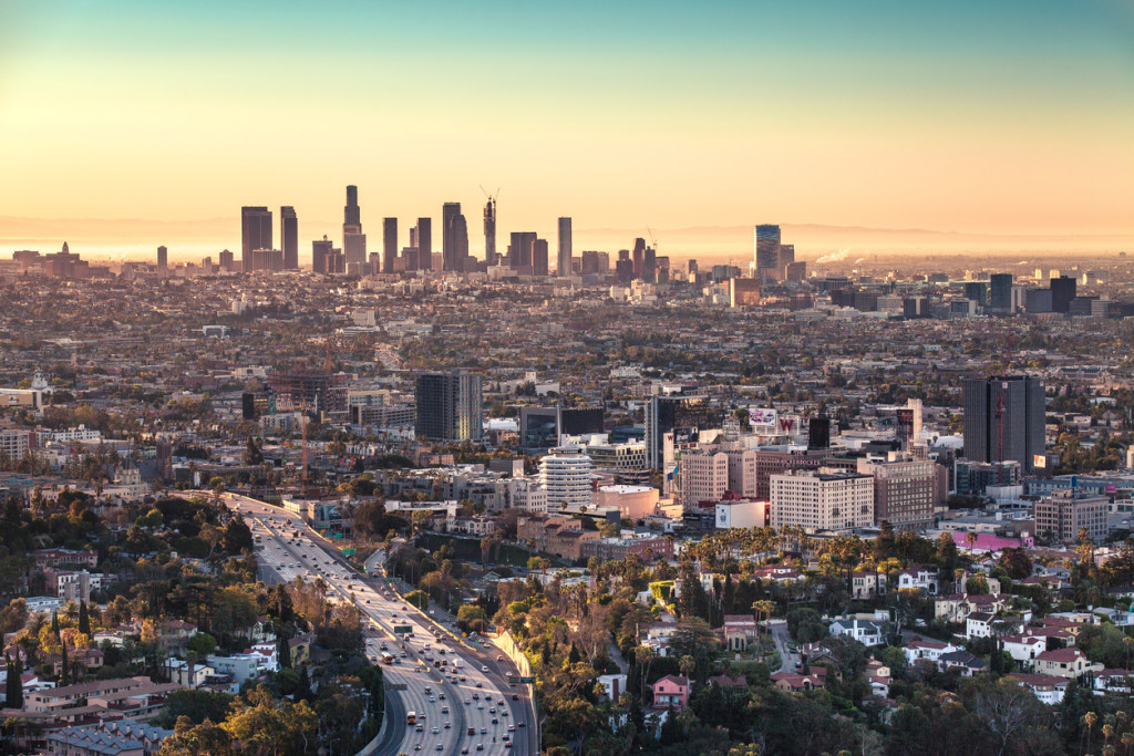 The Downtown Los Angeles skyline and Hollywood at sunrise with a cloudless but partially hazy marine layer sky.
