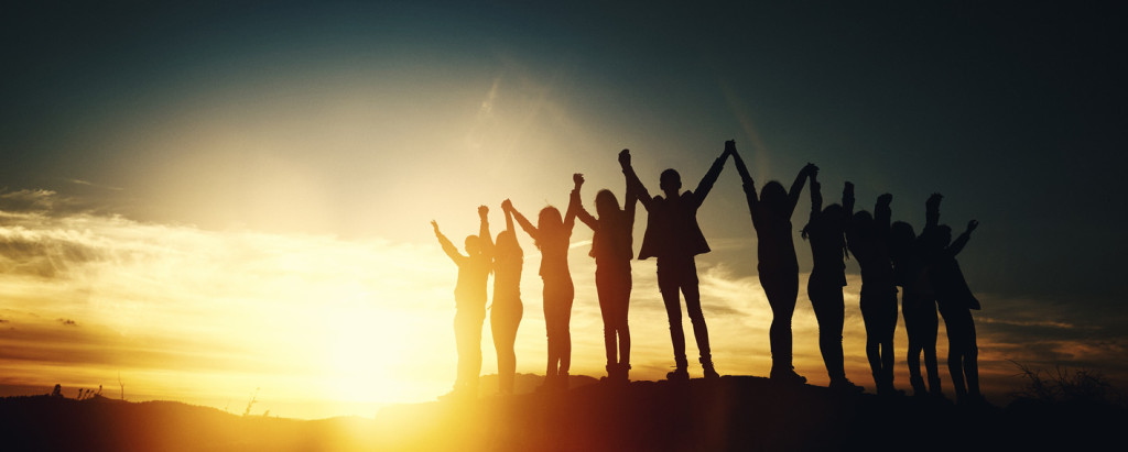 group of people holding hands and feeling together, arms raised in the sky, freedom, friendship and unity concept.