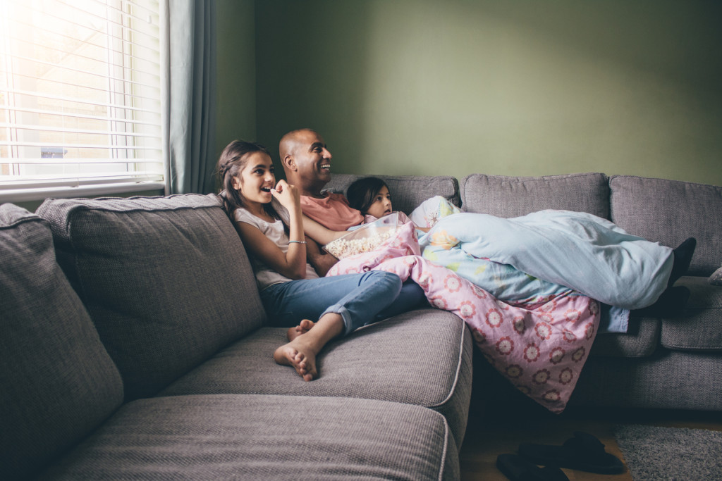 Father curled up on the sofa with his two daughters. They are watching a movie with popcorn.