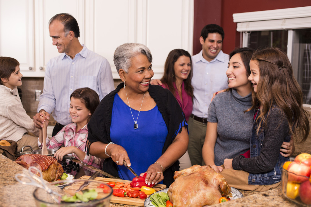 Multi-ethnic group prepare dinner together in home kitchen