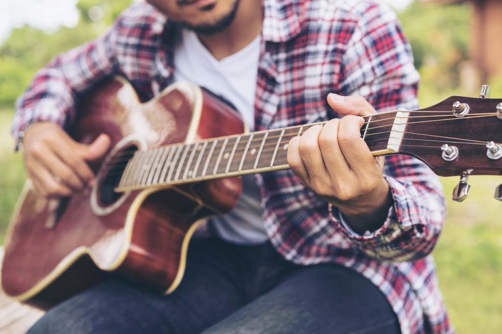 Man 's hand playing guitar, sitting on green grass.