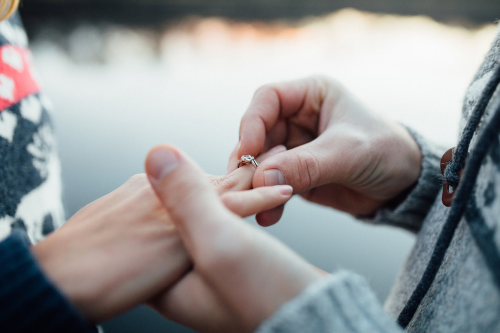 Picture of man putting engagement silver ring on woman hand, outdoor. Seaor river background.