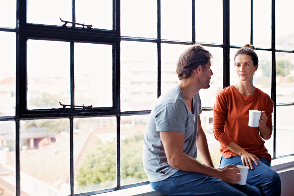 Shot of a happy mature couple sitting on a window sill at home drinking coffee and talking together