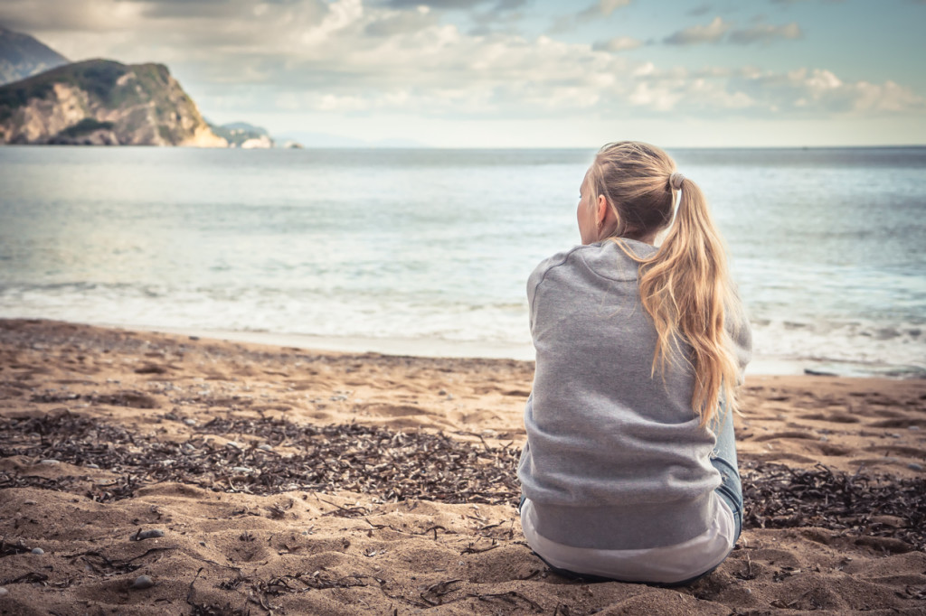 young woman sitting on beach hugging her knees and looking into the distance