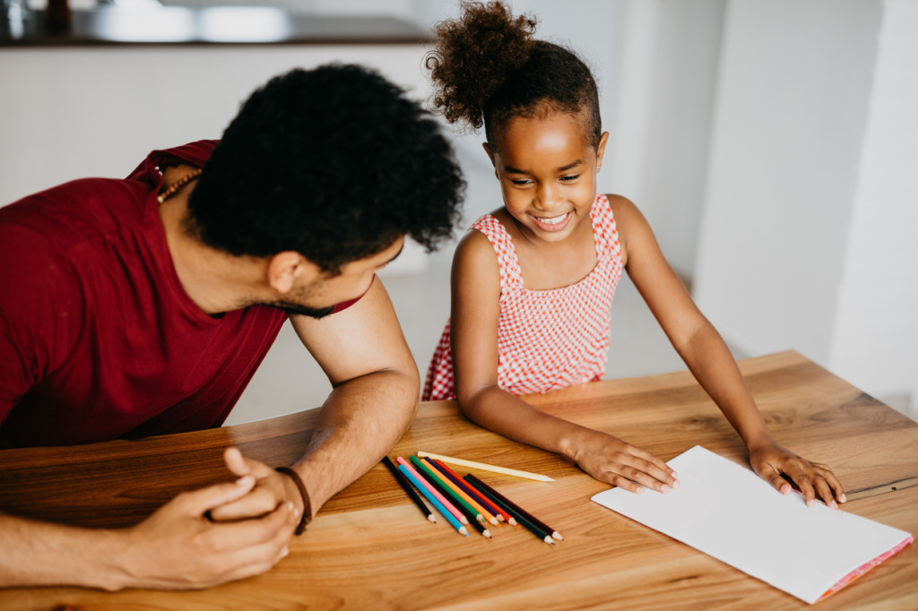 African ethnicity family in the living room at home drawing and having fun together. Life of a single millennial parent. Father and daughter quality time.