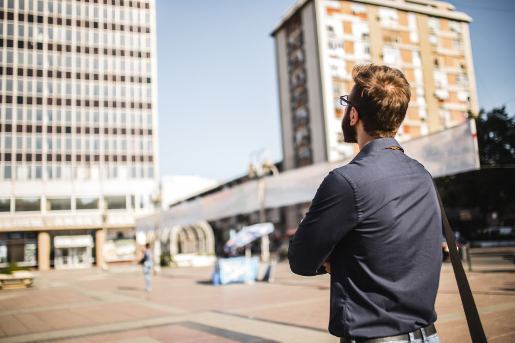 One man, handsome bearded young adult, standing outdoors, rear view.