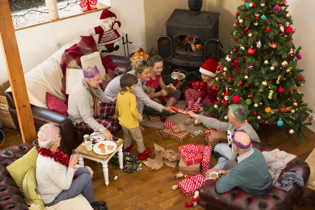 A family are sat around a christmas tree, opening presents and pulling crackers.