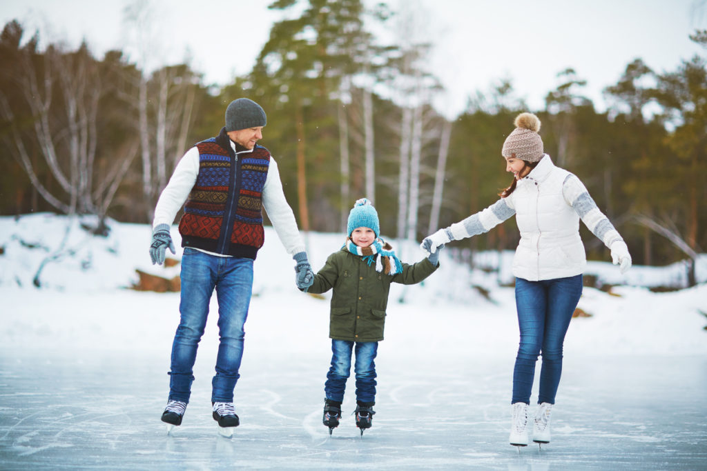 Modern family of father, mother and son skating in natural environment