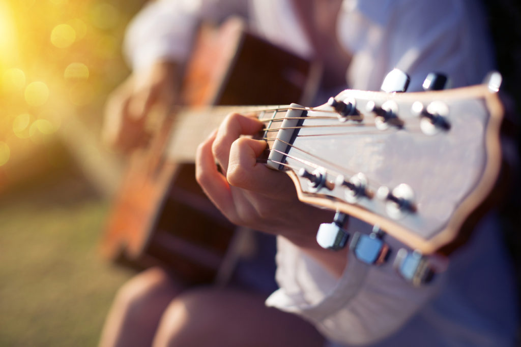 Female hand playing guitar outdoor