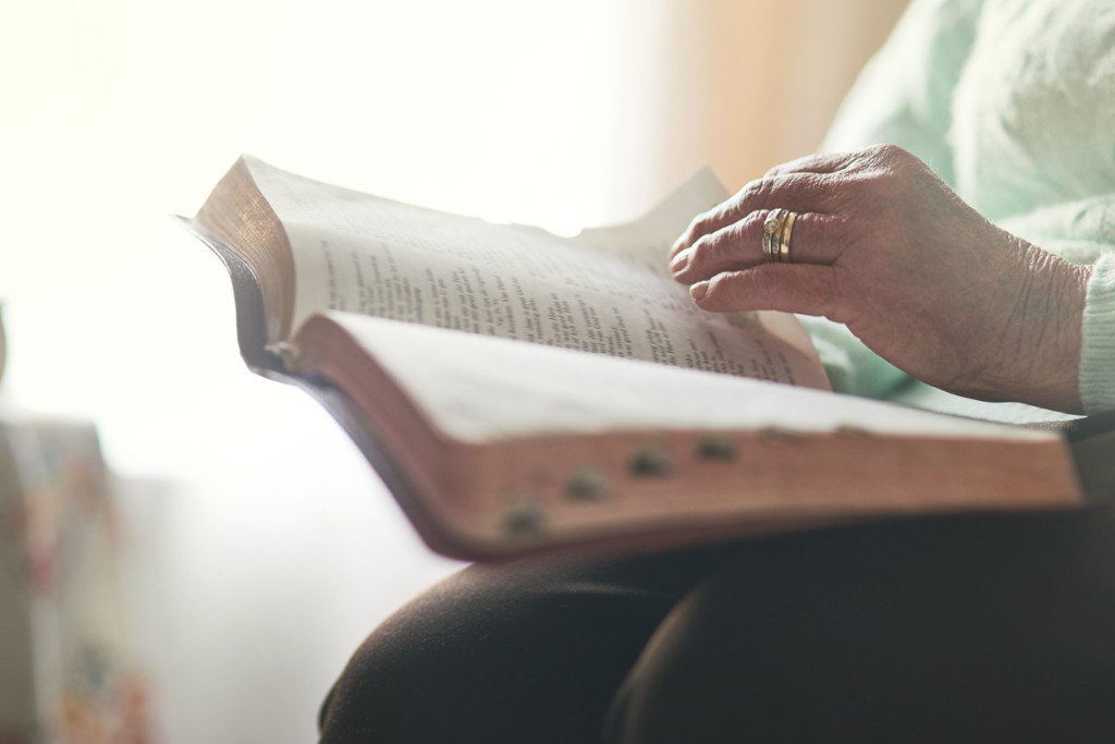 Closeup shot of an unrecognisable woman reading a bible