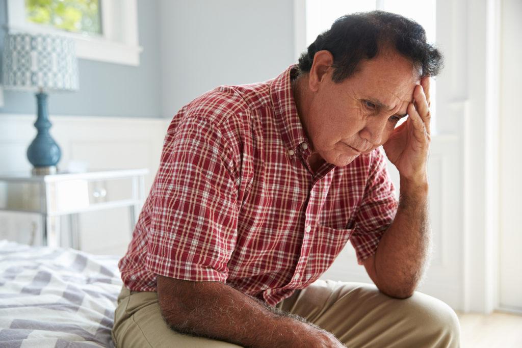 Senior Hispanic Man Sitting On Bed Suffering With Depression