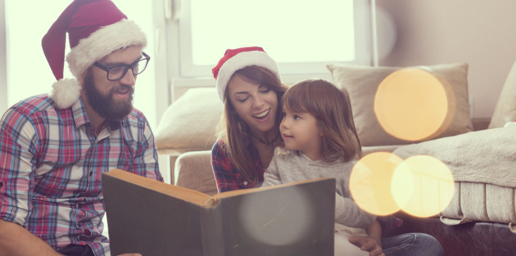 Young parents sitting on the living room floor next to a nicely decorated Christmas tree, mother holding a baby girl in her lap and all together reading a fairy tale. Focus on the baby girl