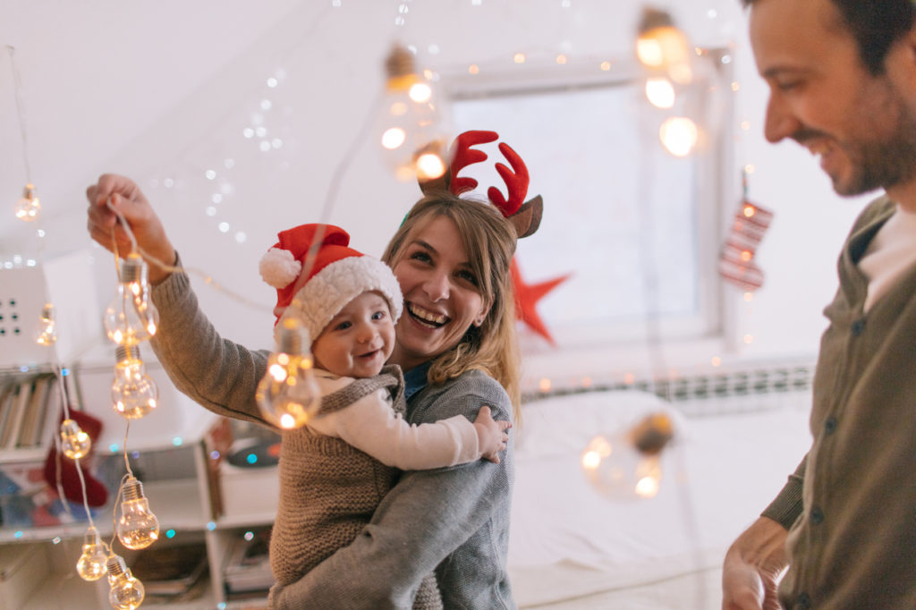 Photo of a cheerful young family with one child, decorating for the first Christmas they are spending together with a baby