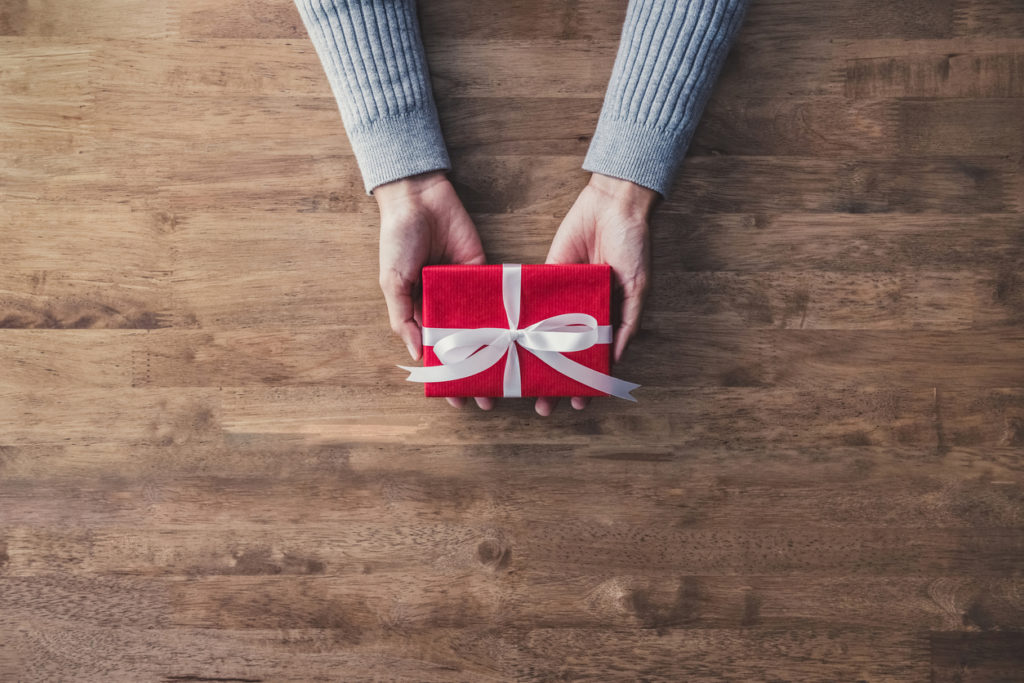 Woman hands in gray sweater on wood table giving red Christmas gift box