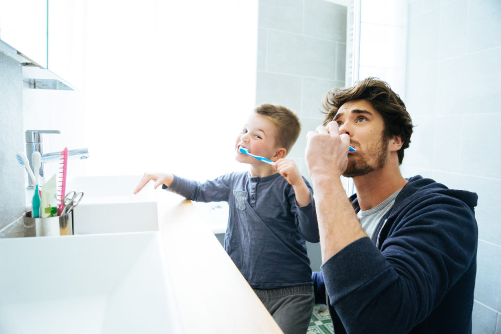 Father And Son Brushing Their Teeth