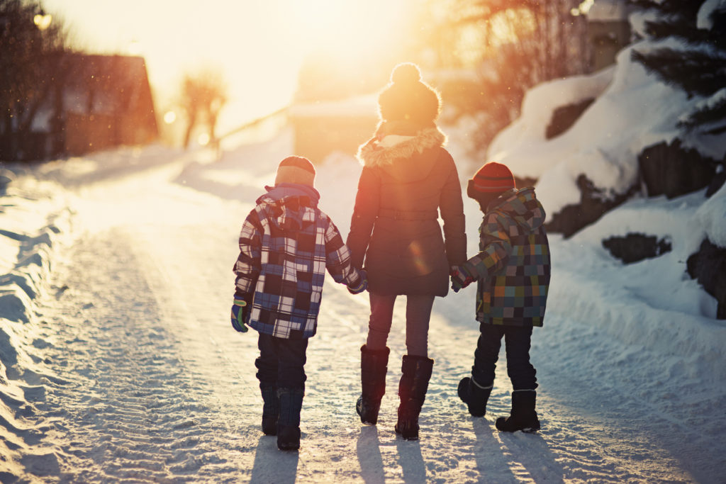 Brothers and sister walking on road on sunny winter evening.