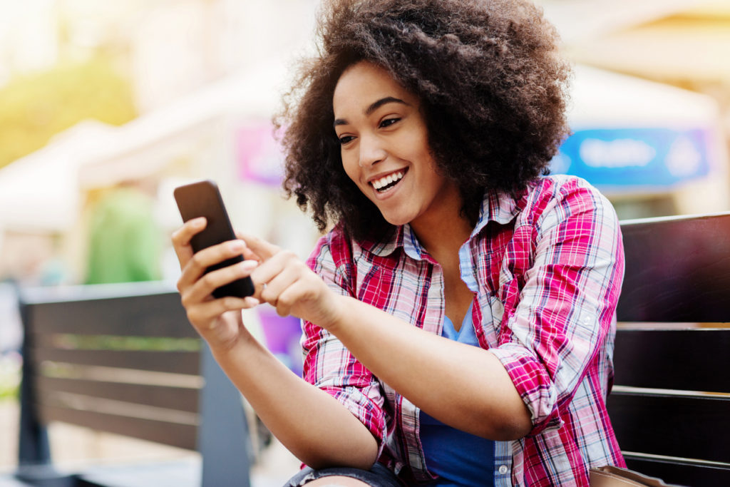 Smiling young African ethnicity woman sitting on a bench outdoors and texting.