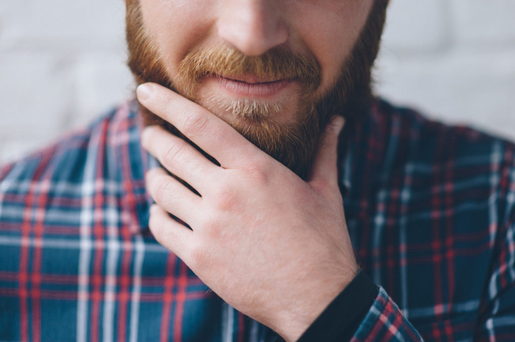 young man in a flannel shirt touches with hand his beard