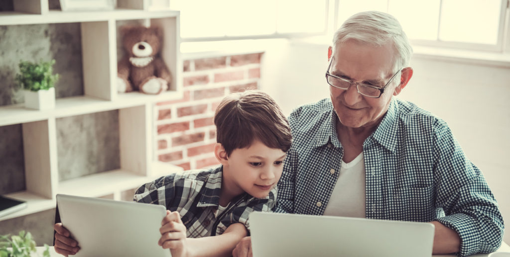 Handsome grandpa and grandson are using gadgets and smiling while spending time together at home