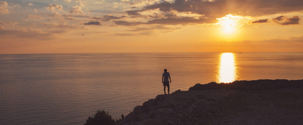 Silhouette of a man standing on the cliff and watching sunset over the sea horizon.