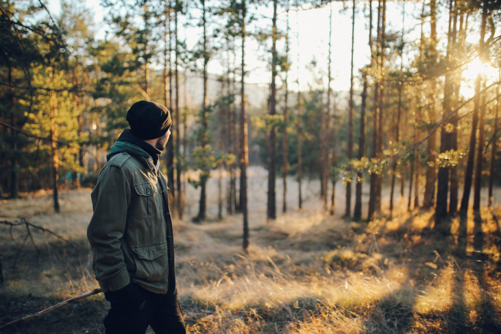 Young man walking in the beautiful forest outdoors