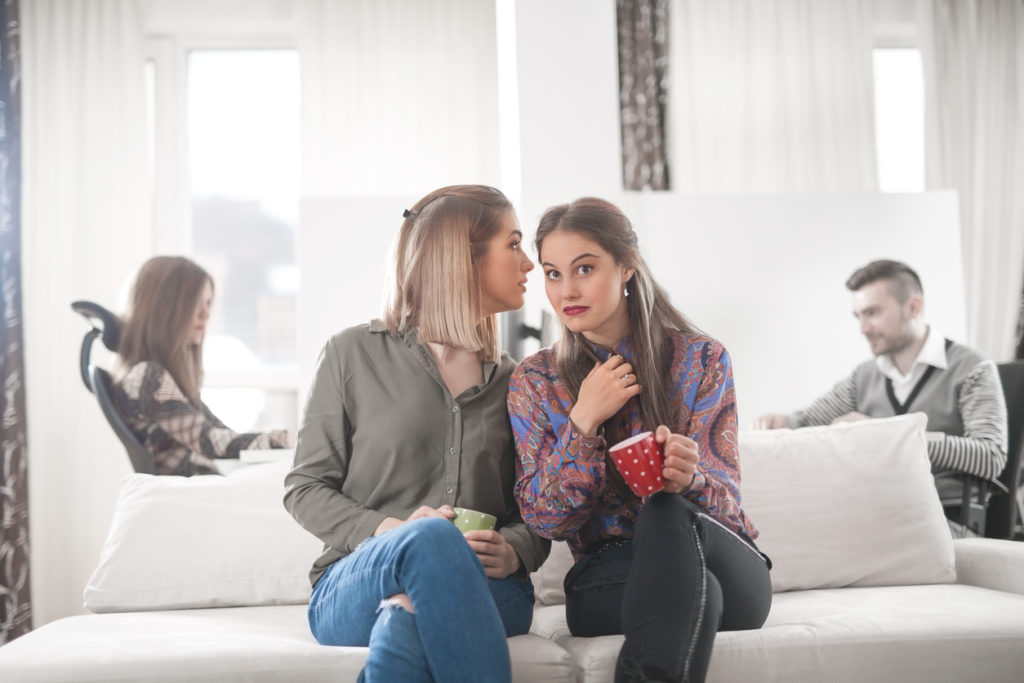 Two young businesswomen are having a coffee and gossip break in the office